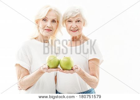 Take care of your health. Waist up portrait of cheerful old women holding green apples and showing it to camera with satisfaction. They are standing and embracing. Isolated