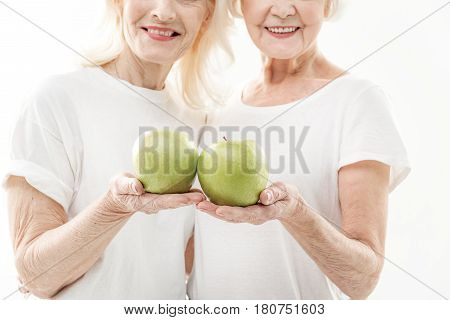 Glad senior female friends are presenting healthy food. They are standing and smiling. Focus on green apples in their hands. Isolated