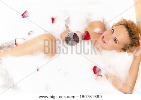 Spa Concepts and Ideas. Sensual Alluring Caucasian Blond Female in Foamy Bathtub Filled with Flowery Petals During Skin and Body Treatment.Passionate Look. Horizontal Image