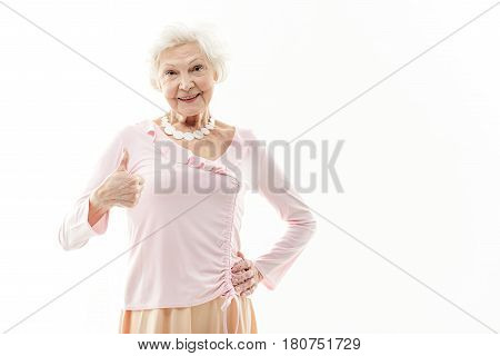 I am okay. Joyful old woman is giving thumb up and smiling. She is standing in stylish dress. Isolated and copy space in right side
