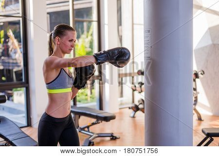 Attractive Female Punching A Bag With Boxing Gloves On.