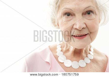 Young by heart. Portrait of glad senior lady with wrinkles over her face. She is looking at camera and smiling. Isolated and copy space in left side