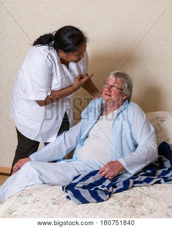 Nurse in old people's home shouting at an elderly man while helping him into bed