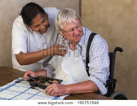 Nurse trying to make an elderly man drink enough water