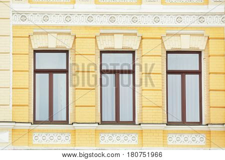 Ornate building with vintage windows and brick wall background