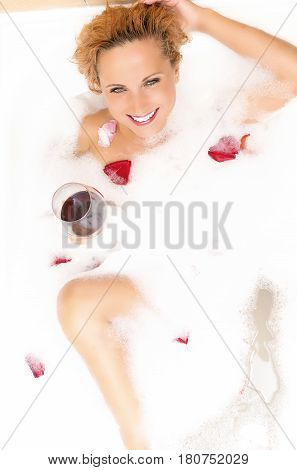 Spa Concepts. Sensual Alluring Sexy Caucasian Blond Female in Foamy Bathtub Filled with Flowery Petals Relaxing Holding a Glass of Red Wine. Passionate Look. Vertical Image