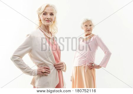 Look at us. Portrait of fashionable senior ladies are posing in elegant dresses. They are standing with arms akimbo and smiling. Isolated
