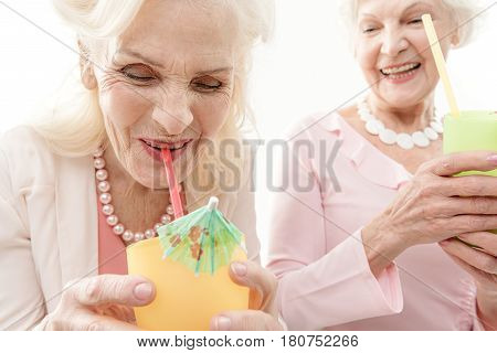 Young by heart. Happy old woman is drinking cocktail and laughing. She is holding cup and keeping tubule in her mouth. Her friend is standing and looking at her with fun