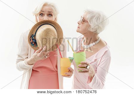 Tell me the truth. Serious old woman is looking at her friend with expectation. Socked lady is covering her mouth by hat while holding glass of cocktail. Isolated
