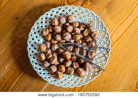 Close up hazelnut. Fresh organic filbert in plate on wooden background