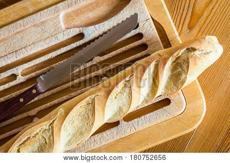 Close up french bread baguette on vintage wooden board with knife