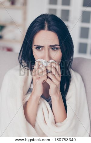 Beautiful Sad Depressed Young Woman Touches Her Nose With Napkin. She Sits With Coverlet On Sofa At