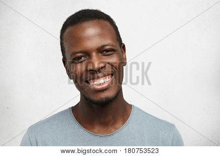 Headshot Of Handsome Young Afro American Male Looking At Camera With Broad Friendly Smile, Enjoying