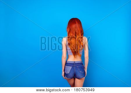 Back View Portrait Of  Sexual Stylish Girl With Long Ginger Fair Hair  Wearing In Short Jeans Shorts