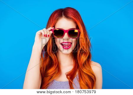 Funny Carefree Girl With Ginger Hair Holding Sunglasses And Licking Pink Lips While Standing On Blue