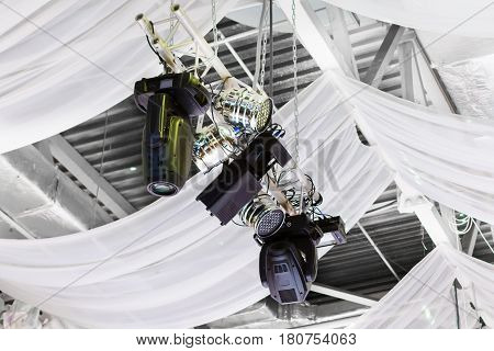 Bright floodlights attached to a steel frame. Horizontal view of floodlights attached to a frame, used inside a hall.