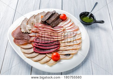 Meat plate with delicious pieces of sliced ham, cherry tomatoes and meat with sauce on white wooden background.