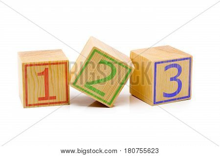 Three brown wooden cubes lined up in a row with numbers one two and three over white background - education or counting concept