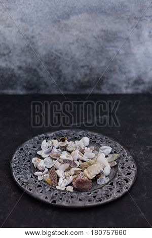 Seashells of various shapes and colors placed in flat metal plate with carved frame on dark tabletop against gray wall