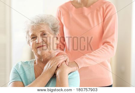 Young girl hugging old woman, closeup