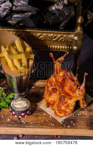 The quails fried on coals of a carcass of quails. Are served with onions, red pepper, parsley and spices salad, French fries and garlick sauce