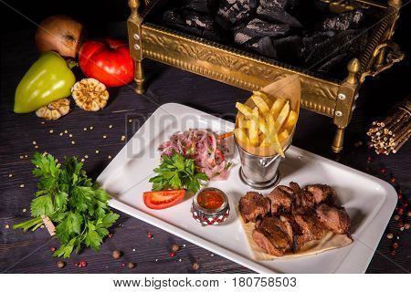 A shish kebab from mutton, with sauce, onions salad, tomatoes and French fries