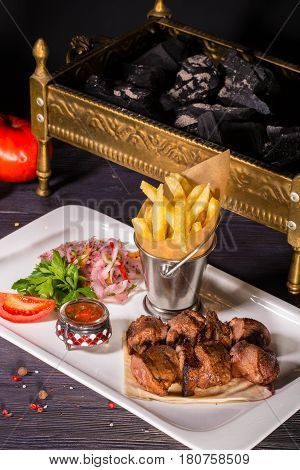 Shish kebab pieces from mutton, is served with onions salad, tomatoes, sauce and French fries