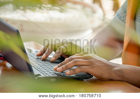 hands typing on laptop keyboard. Black person working with computer outdoors blurred background. Freelancer at work. Selective focus