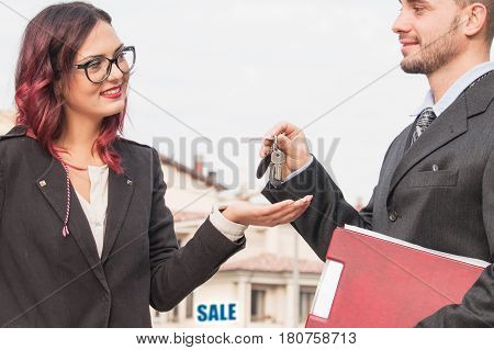 real estate property sale. real estate agent hands over new home keys to woman customer. concept of happy lady buying a new house and relocating