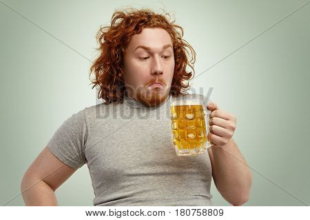 Clueless Red Haired Young Man With Curly Hair Holding Glass Of Light Beer, Looking At It, Having Con
