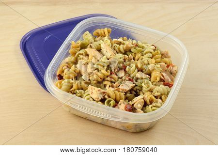 Baked salmon pasta salad with spiral rotini vegetable pasta in plastic storage container