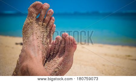 Male Cross Feet at the Sandy Beach, Ocean in Background, Bali Indonesia