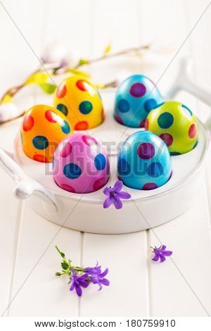 Colorfu Easter eggs with spring flowers decorating table