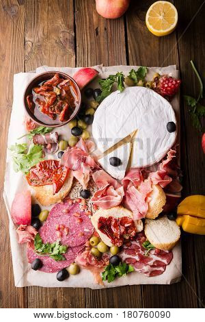 Still life food and drink holidays concept. Assortment of spanish tapas or italian antipasti (jamon prosciutto chorizo salami) on a wodden board (rustic style). top view . Jamon. Brie cheese.
