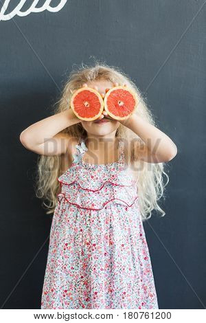 A little girl with curly hair holds grapefruit halves in her hands