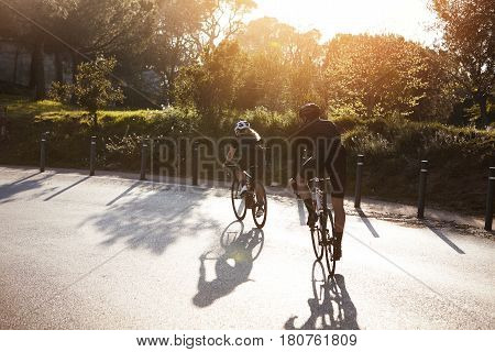 Back View Of Wife And Husband Doing Sports Riding Racing Bicycles. Young Couple Wearing Special Acti
