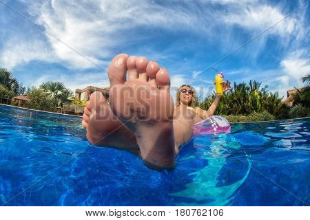 Young woman with perfect clean female feet has a fun in swimming pool with cocktails