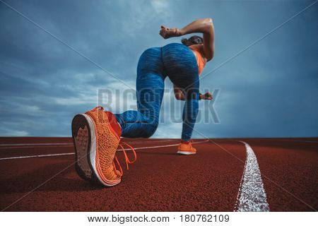 Close up wide angle view of a female sprinter athlete getting ready to start a race on a tartan racetrack