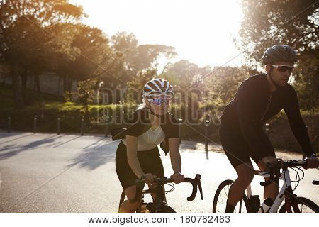 Active People. Image In Motion Of Two Bicyclists Riding Along Road Wearing Sporty Clothes, Sunglasse