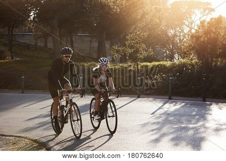 Healthy lifestyle. Outdoor picture of active and sporty couple on bike ride on suburban street. Good friends having calm holiday trip on their racing bicycles wearing fitness clothes and shades poster