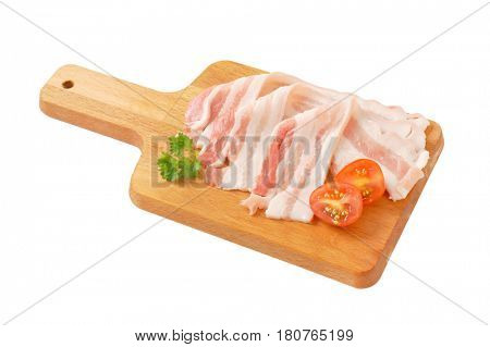 Thin slices of fresh streaky bacon on cutting board