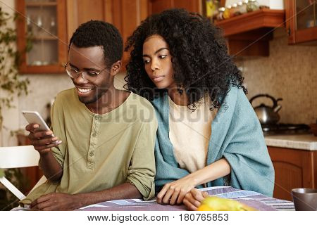Handsome Dark-skinned Male Browsing Social Networks On Smart Phone Having Happy Look, Not Noticing H