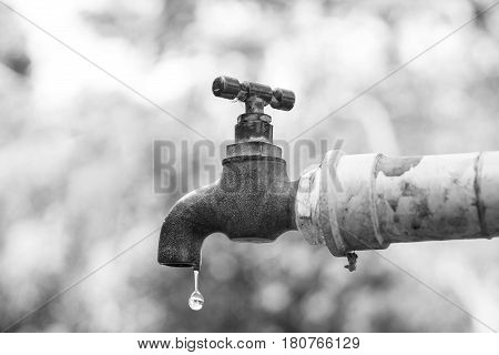 A faucet with a water drop / Water consumption and shortage concept