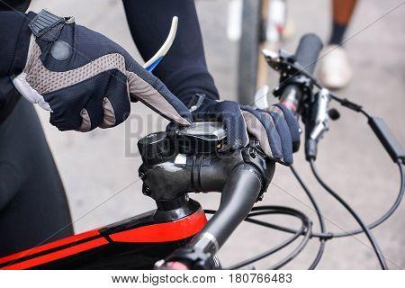 A mountain bike cyclist adjusting bike computer installed on a bicycle's handlebar