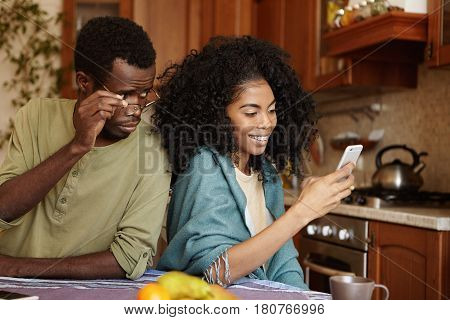 Dishonest Attractive African American Woman Reading Messages On Mobile Phone, Having Happy Carefree