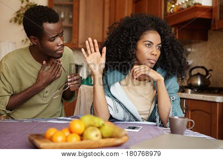 African Couple Having Quarrel At Home. Unhappy Husband Apologizing For An Affair To His Offended Ang