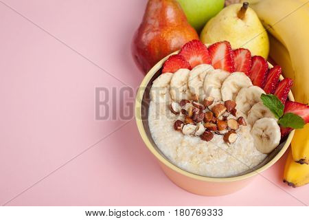 Bowl Of Oatmeal With A Banana, Strawberries, Almonds, Hazelnuts And Butter On A Pink Background. Hot