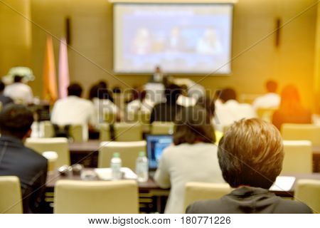 Blurred Image Of Education People, Business People And Students Sitting In Large Hal With Screen And