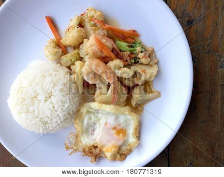 Stir-fry Vegetables With Bean Curd And Shrimp In White Dish With Rice And Fried Egg On Wooden Backgr