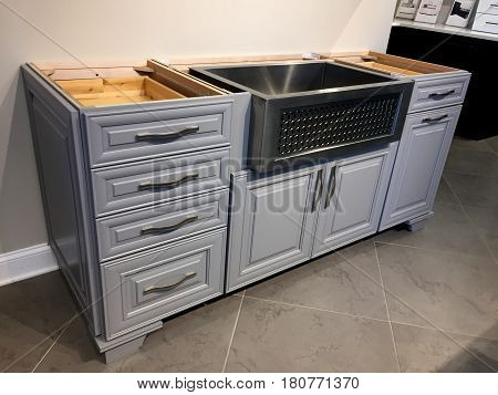Kitchen cabinet. Contemporary full overlay kitchen cabinet with stainless steel sink. Handles on kitchen cabinet. Farm kitchen cabinet design. Gray wooden kitchen cabinet on tile floor.